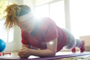 Portrait of young woman working out on yoga mat in fitness studio